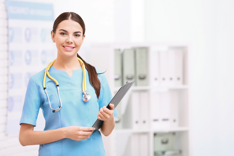 Portrait of medical assistant with stethoscope and clipboard in hospital. Space for text